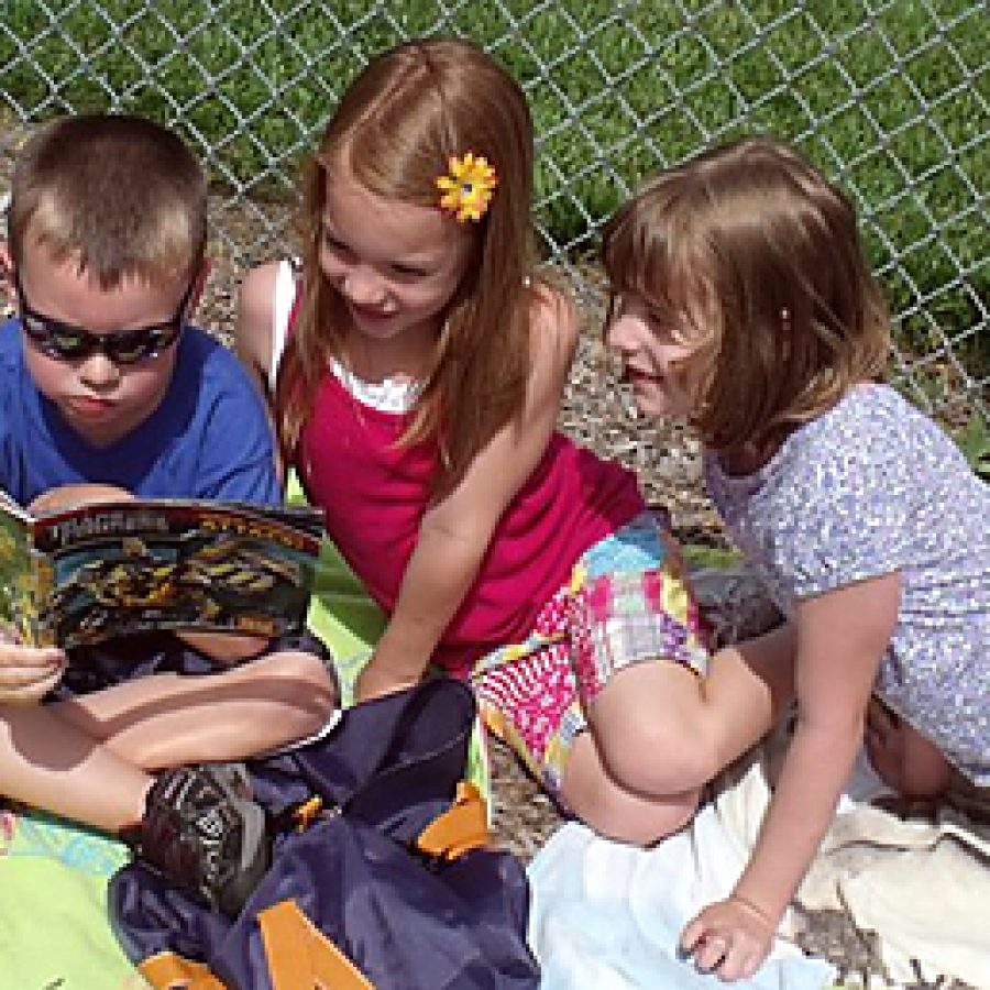 Mehlville School District Summer Academy kindergartners, from left, Gavin Armistead, Teresa Laramie and Abby Weibel, participate in a beach-themed reading event on June 16 to raise money for the tornado victims in Joplin.