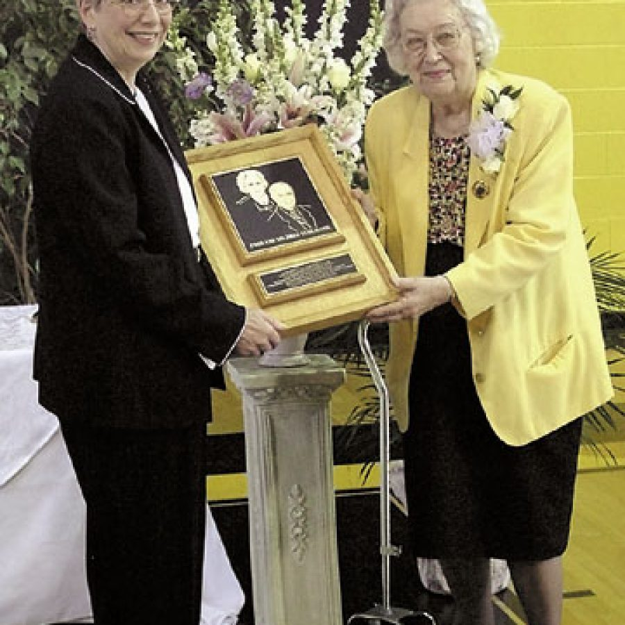 Lutheran High School Association President Judith Meyer, left, presents a plaque to Mildred Kuhlmann in recognition of the Kuhlmann family's support of Lutheran High School South.