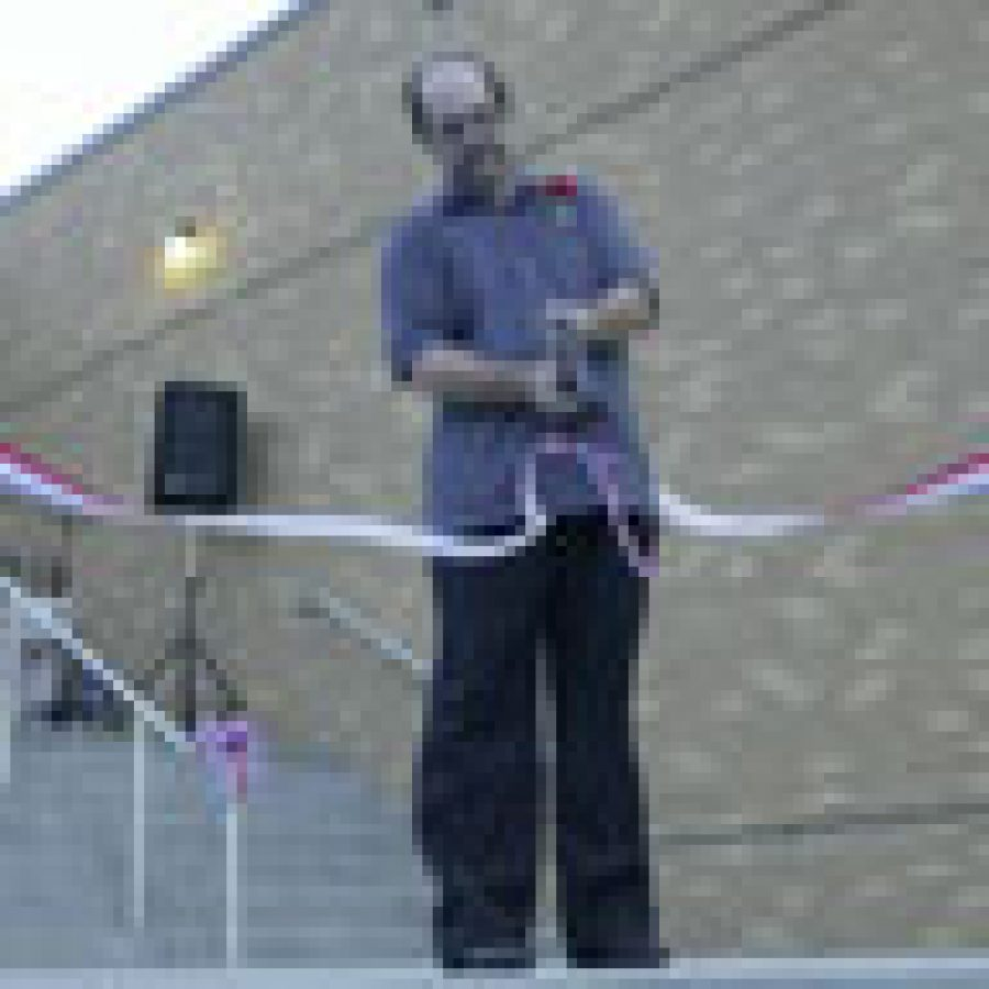Head custodian Dave Taylor cuts the ribbon marking the grand re-opening of Washington Middle School. Taylor was recognized for service above and beyond the call of duty during the construction process.