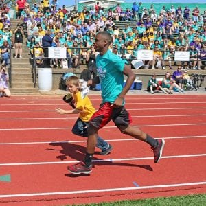 A Special Olympics buddy and his athlete run on the track during the annual Special Olympics at Mehlville High School in May.