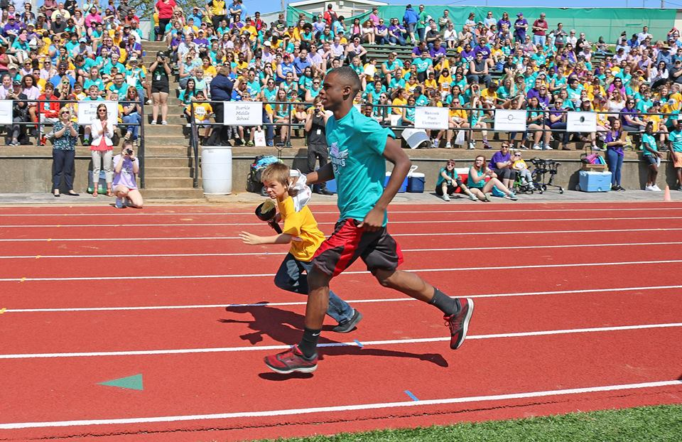 A+Special+Olympics+buddy+and+his+athlete+run+on+the+track+during+the+annual+Special+Olympics+at+Mehlville+High+School+in+May.