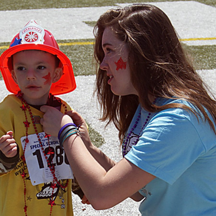 Mehlville High freshman Kaitlyn Krejci pins a ribbon on the shirt of her buddy, Point Elementary kindergartner Dallas Wallace, at MHS' 14th annual Special Olympics held on May 4 at Jack Jordan Stadium on the MHS campus.
