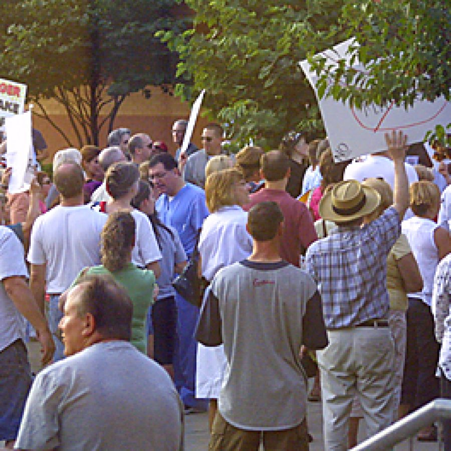 Hundreds of placard-bearing residents demonstrated outside Bernard Middle School after being shut out of a town-hall meeting on 'Aging in America' sponsored by U.S. Rep. Russ Carnahan, D-St. Louis. Bill Milligan photo
