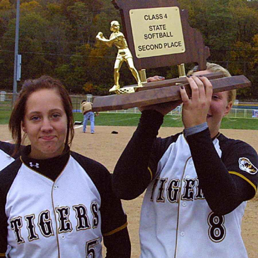 Senior Maggie Ruckenbrod, right, hoists the Missouri Class 4 States second-place trophy above her head as senior pitcher Kari McIvers look expresses the teams disappointment with the outcome. Bill Milligan photo