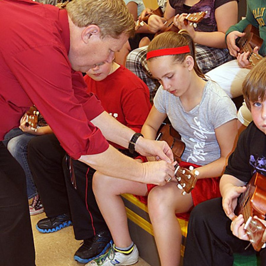 Fred Willman helps Oakville Elementary School fifth-grader Madyson McQuilling during the ukulele workshop he presented at no cost for the school's fifth-graders.